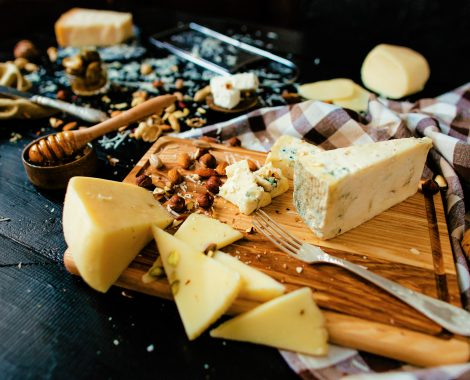 Assortment of cheese. Composition of different varieties of cheese with honey, nuts, olives on rustic dark wooden table